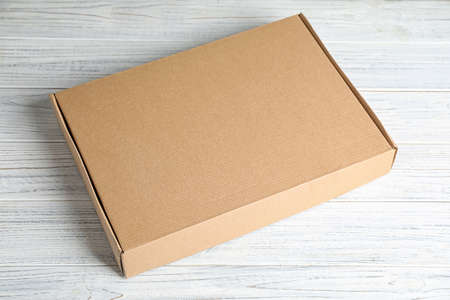 Closed cardboard box on white wooden table Stock Photo