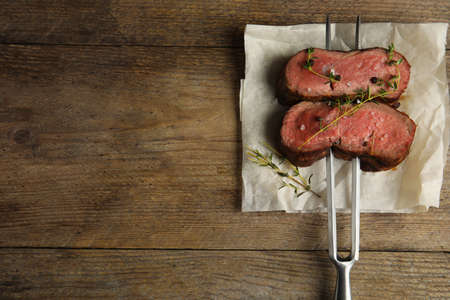 Fork with slices of meat on wooden table, top view. Space for text Stock Photo
