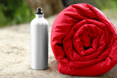 Rolled sleeping bag and bottle on sand