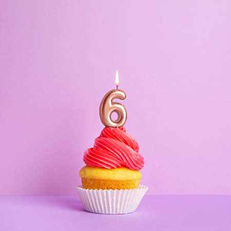 Birthday cupcake with number six candle on violet background Stock fotó