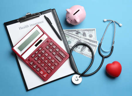 Flat lay composition with health insurance form, calculator and stethoscope on blue background