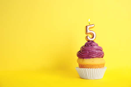 Birthday cupcake with number five candle on yellow background, space for text