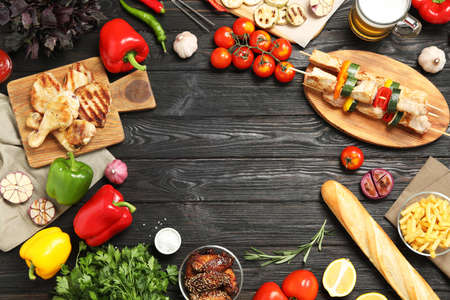 Frame of barbecued meat and vegetables on black wooden table, flat lay. Space for text