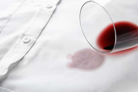 Overturned glass and spilled exquisite red wine on white shirt. Space for text 写真素材 - 130133463