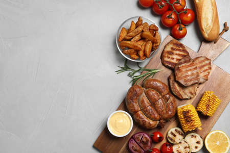 Flat lay composition with barbecued meat and vegetables on light table. Space for text Stock Photo