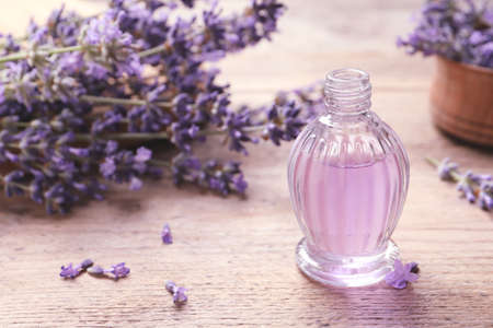 Glass bottle of natural cosmetic oil and lavender flowers on wooden table, space for text Imagens