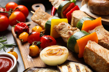 Barbecued meat and vegetables on table, closeup