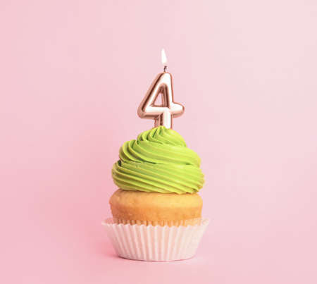 Birthday cupcake with number four candle on pink background Stock fotó