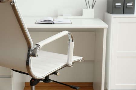 Modern office chair near table indoors, closeup. Stylish workplace interior