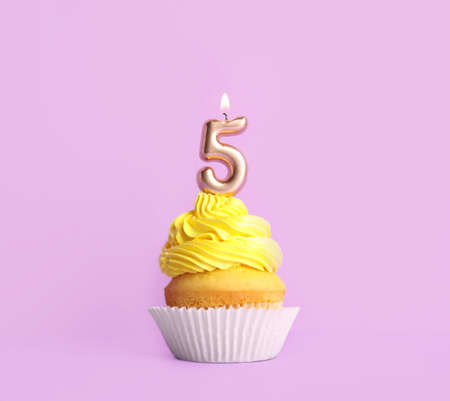Birthday cupcake with number five candle on violet background