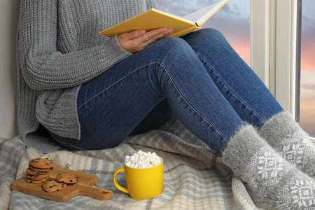 Woman with cup of hot cocoa reading book on window sill, closeup. Winter drink Stok Fotoğraf