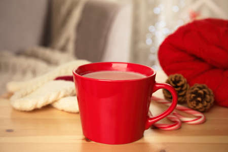 Cup of hot cocoa on wooden table indoors. Winter drink