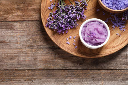 Plate with natural cosmetic products and lavender flowers on wooden table, top view. Space for text