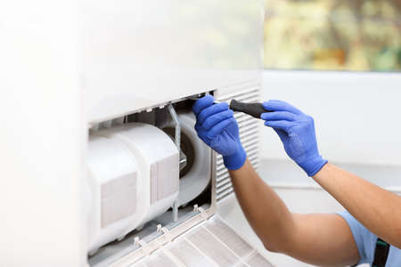Professional technician maintaining modern air conditioner indoors, closeup. Space for text