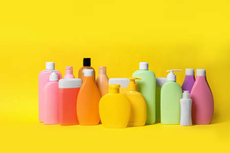 Different bottles of shampoo on yellow background. Natural cosmetic products Imagens