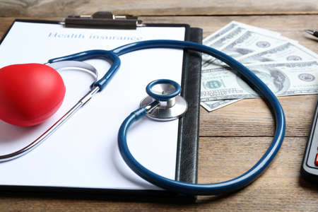 Health insurance form, red heart with stethoscope and money on wooden surface