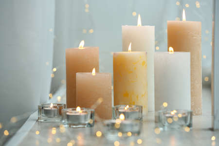 Beautiful burning candles and fairy lights on windowsill indoors