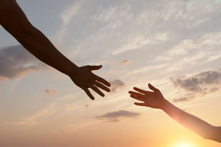 Man giving hand to woman outdoors, closeup. Help and support concept