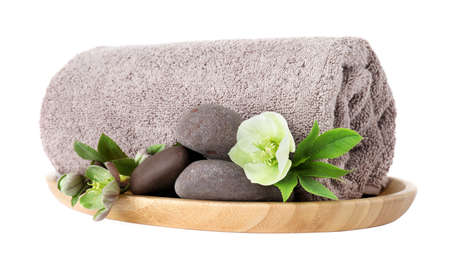 Wooden tray with towel, spa stones and flowers isolated on white