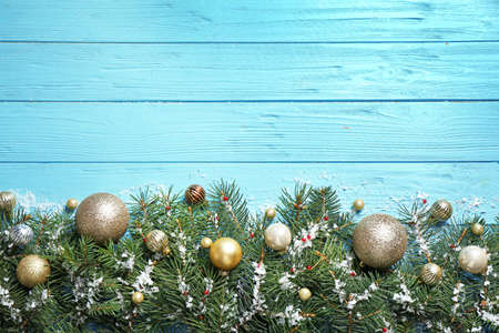 Fir tree branches with Christmas decoration on light blue wooden background, flat lay. Space for text Stockfoto