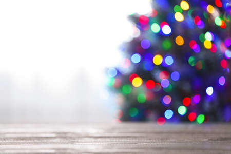 Blurred view of beautiful Christmas tree with colorful lights near window indoors, focus on wooden table. Space for text Stockfoto