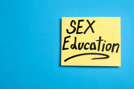 """Note with phrase """"SEX EDUCATION"""" on blue background, top view. Space for text"""