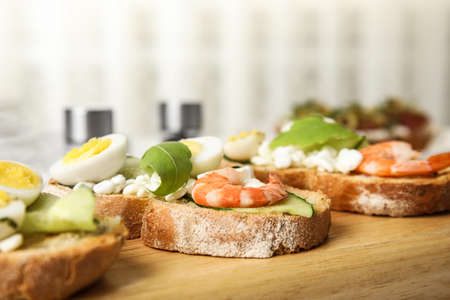 Cutting board of delicious bruschettas with shrimps on kitchen table