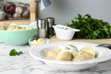 Delicious cooked dumplings with sour cream on white marble table Stok Fotoğraf