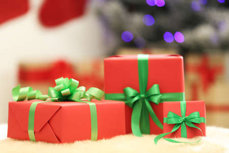 Christmas gifts on fuzzy rug against blurred background