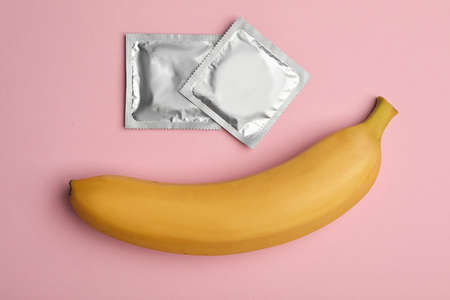 Condoms with banana on pink background, flat lay. Safe