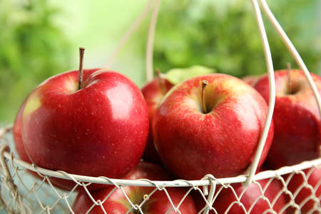 Metal basket with ripe juicy red apples against blurred background, closeup Stockfoto
