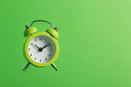 Alarm clock on green background. Space for text Stock Photo