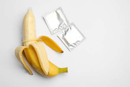 Banana with condoms on white background, top view. Safe
