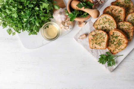 Slices of toasted bread with garlic and herbs served on white wooden table, flat lay. Space for text