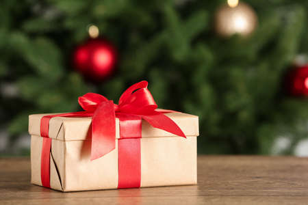 Christmas gift on table against blurred background Фото со стока