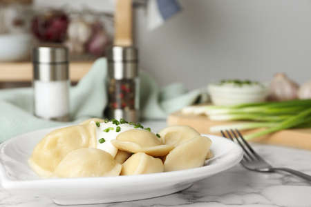 Delicious cooked dumplings with sour cream on white marble table, closeup