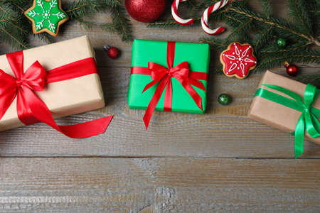 Flat lay composition with Christmas gifts on wooden background. Space for text