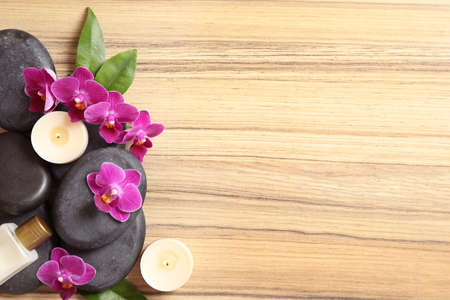 Flat lay composition with spa stones and orchid flowers on wooden background. Space for text Reklamní fotografie - 130134053