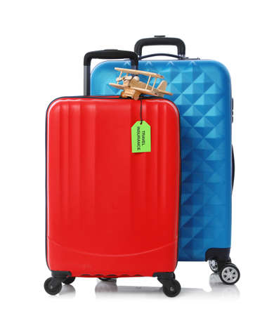 Red and blue suitcases with TRAVEL INSURANCE label on white background