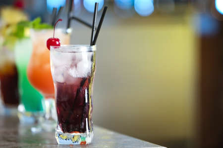 Row of different fresh alcoholic cocktails on bar counter