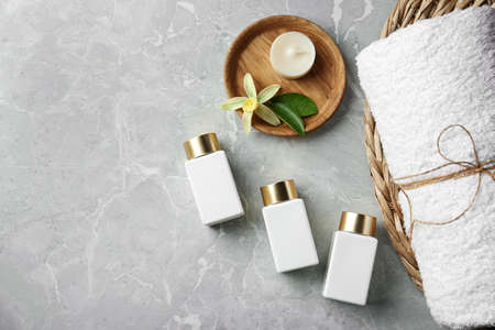 Flat lay composition with cosmetic products on grey stone table, space for text. Spa therapy