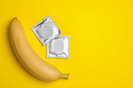 Condoms with banana and space for text on yellow background, flat lay. Safe sex