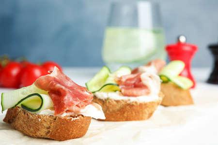 Tasty bruschettas with prosciutto served on table Stock fotó