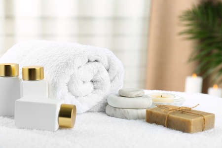 Composition with cosmetic products on white towel indoors. Spa therapy