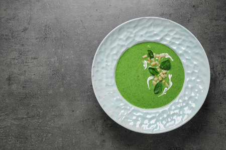 Plate of healthy green soup with fresh spinach on grey table, top view. Space for text