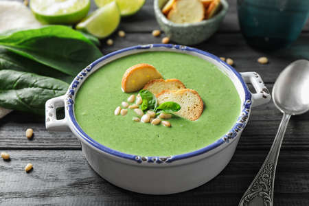 Bowl of healthy green soup with fresh spinach on grey wooden table