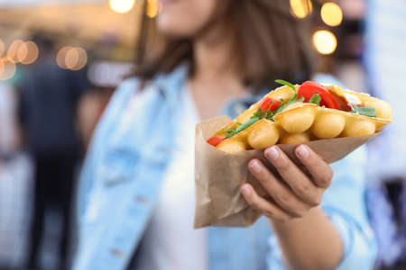 Young woman holding delicious bubble waffle with tomato and arugula outdoors, closeup