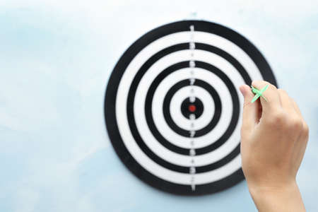 Woman throwing green arrow at dart board on light blue background, closeup. Space for text