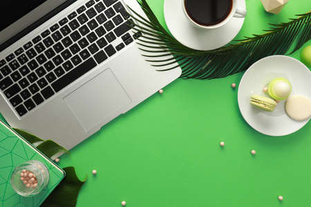 Flat lay composition with laptop on green background. Stock Photo