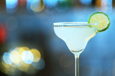 Glass of fresh alcoholic cocktail against blurred background. Space for text Stock Photo